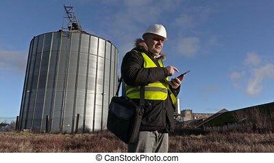 Engineer take picture on phone near aluminium tank
