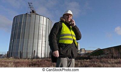 Engineer talking on phone near aluminium tank