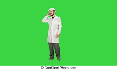 Engineer talking on the phone on a construction site on a Green Screen, Chroma Key.