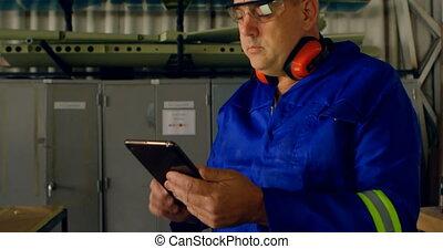 Male engineer using digital tablet in aircraft hangar 4k