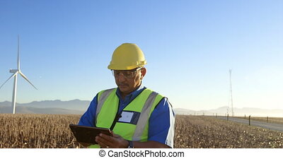 Engineer using digital tablet in the wind farm 4k - Male...
