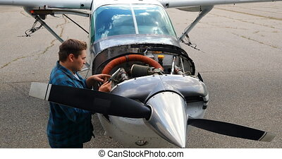 Engineer using digital tablet while servicing aircraft engine 4k