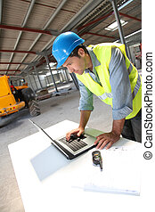 Engineer using laptop computer on construction site