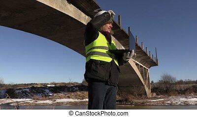 Engineer using laptop near the bridge in winter