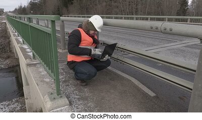 Engineer using laptop on the bridge