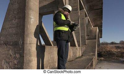 Engineer using laptop under the bridge