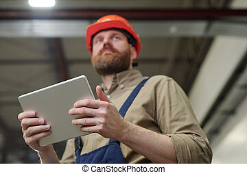 Engineer using tablet at factory