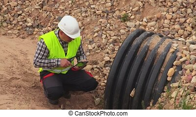 Engineer using tablet at the drainage ditch