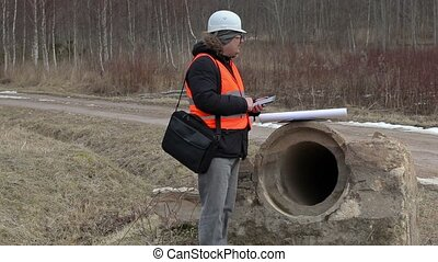 Engineer using tablet PC at the concrete pipes