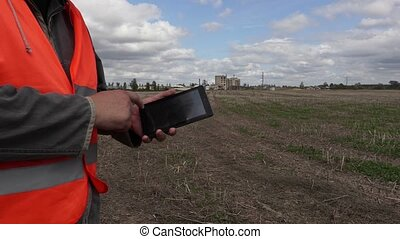 Engineer using tablet PC on the field near factory