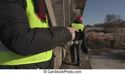 Engineer using tablet PC under the bridge