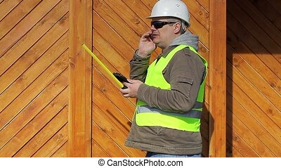 Engineer with a tape measure and cell phone