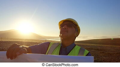 Engineer with blueprint standing in the wind farm 4k