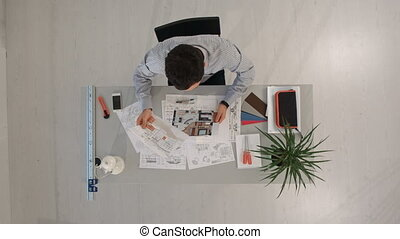 Engineer with blueprints of object and laptop. Top view