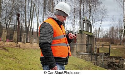 Engineer with cell phone at power