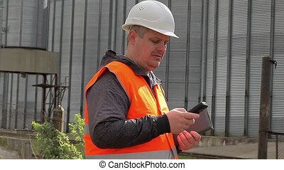Engineer with cell phone at the factory