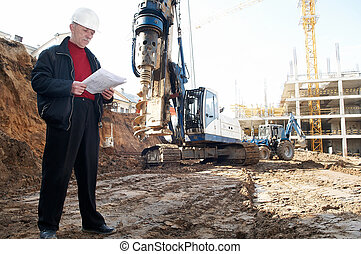 engineer with documentation at construction site - builder...