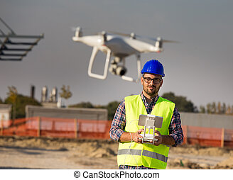 Engineer with drone at building site - Portrait of engineer ...