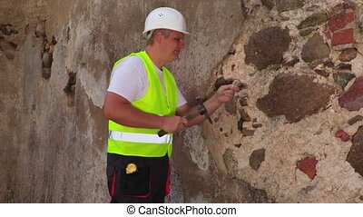 Engineer with hammer checking plaster of old wall