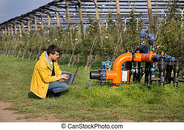 Engineer with irrigation system in orchard - Young engineer ...