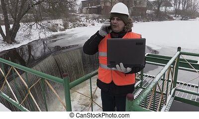 Engineer with laptop and phone near floodgate