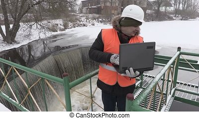 Engineer with laptop checking floodgate