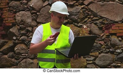 Engineer with sample of old brick wall