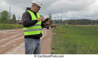 Engineer with tablet PC in road