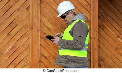 Engineer with tape measure and tablet PC near wooden...