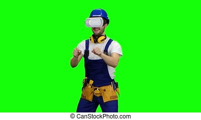 Engineer with virtual reality glasses looks at the building. Green screen