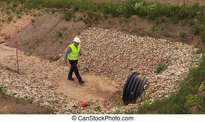 Engineer with walkie talkie near pipe in the deep ditch