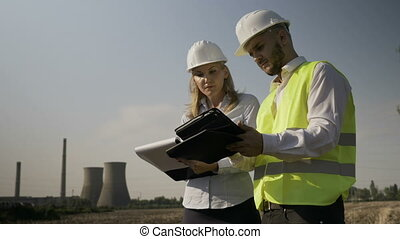 Engineer woman and young foreman analyzing industrial field plans and completing on clipboard work progress report near oil gas refinery