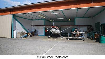 Engineer working in aerospace hangar on a sunny day 4k