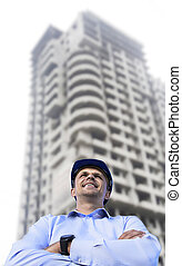 Engineer working on a building site wearing a protective helmet standing on the building background.