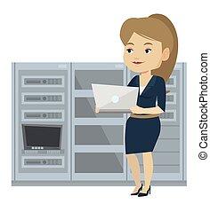 Engineer working on laptop in network server room.