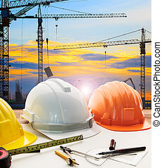 engineer working table plan, home model and writing tool equipment against building construction crane with evening dusky sky