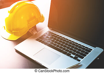 Engineer working table with computer and safety helmet