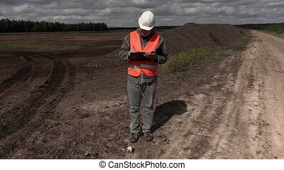 Engineer writes and walking in peat bog