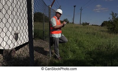 Engineer writing near fence