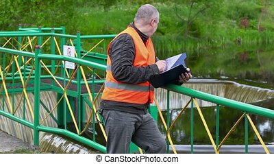 Engineer writing near floodgate