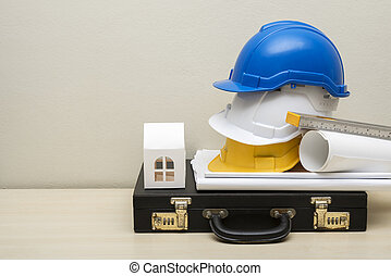 Engineering accessories, helmets, house paper model, business bag, blueprint, on wood table with white concrete wall background. Picture for add text message. Backdrop for design art work.