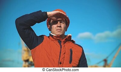 Engineering builder man Consulting People on construction site holding blueprint in his hand. Building inspector. Senior engineer Winter Jacket man lifestyle in suit and helmet outdoor . construction concept winter man in helmet
