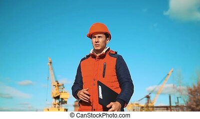 Engineering builder man Consulting People on construction site holding blueprint in his hand. Building inspector. Senior engineer Winter Jacket man in suit and helmet outdoor. construction concept winter lifestyle man in helmet