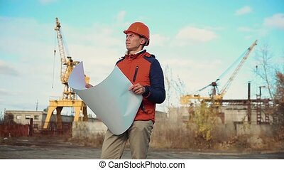 Engineering builder man Consulting People on construction site holding blueprint in his hand. Building inspector lifestyle . Senior engineer Winter Jacket man in suit and helmet outdoor . construction concept winter man in helmet