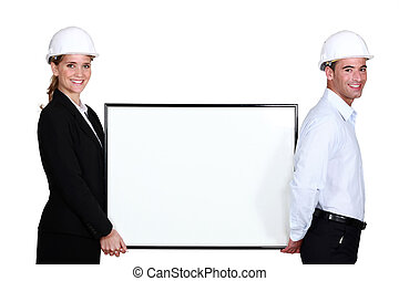 Engineering couple with a board left blank for your message