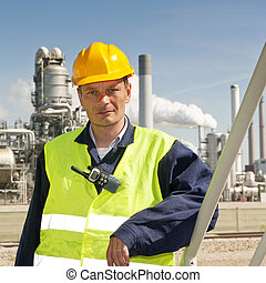 Engineering - Engineer poses casually in front of a refinery...