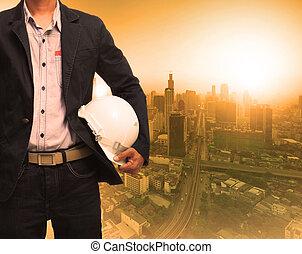 engineering man and sun light behind urban construction backgrou