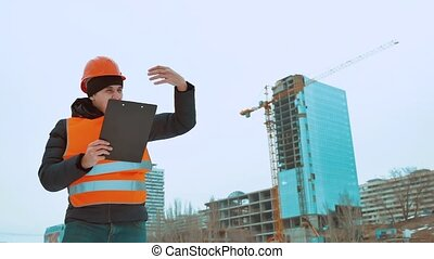 Engineering man Consulting People on construction site holding blueprint in his hand. Building inspector. Senior engineer Winter Jacket man in suit and helmet outdoor. construction concept lifestyle winter man in helmet