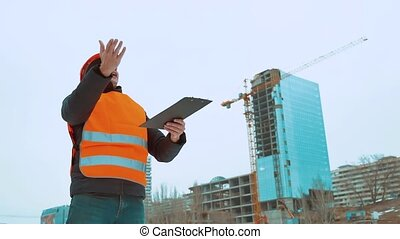 Engineering man Consulting People on construction site holding blueprint in his hand. Building inspector. Senior engineer Winter Jacket man in suit and helmet outdoor. lifestyle construction concept winter man in helmet