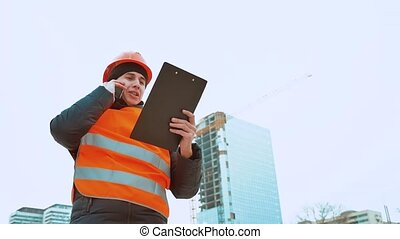 Engineering man Consulting People on construction site holding blueprint in his hand. Building inspector. Senior engineer Winter Jacket man in suit and helmet lifestyle outdoor. construction concept winter man in helmet